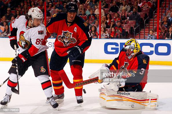 Goaltender Scott Clemmensen of the Florida Panthers defends the net with the help of teammate Filip Kuba against Cory Conacher of the Ottawa Senators...