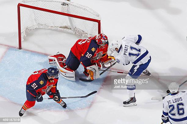 Goaltender Scott Clemmensen of the Florida Panthers stops a shot by Tom Pyatt of the Tampa Bay Lightning at the BBT Center on December 23 2013 in...