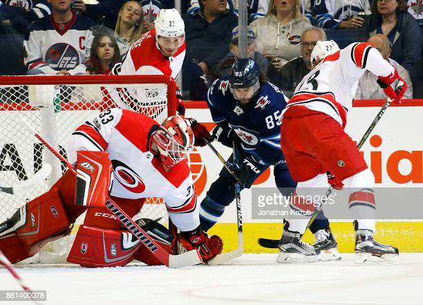 Goaltender Scott Darling of the Carolina Hurricanes covers up the puck in the crease as Mathieu Perreault of the Winnipeg Jets looks on during first...