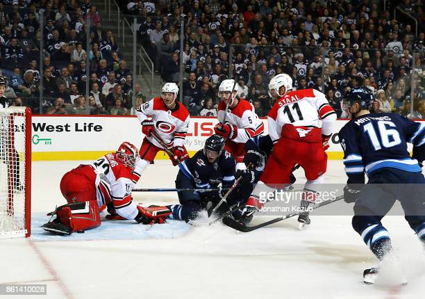 Goaltender Scott Darling of the Carolina Hurricanes makes a pad save in the crease as Andrew Copp of the Winnipeg Jets looks on during second period...