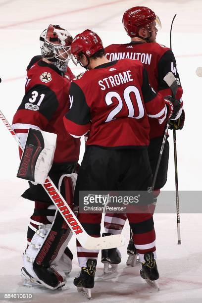 Goaltender Scott Wedgewood of the Arizona Coyotes is congratulated for his shutout by Dylan Strome following the NHL game against the New Jersey...