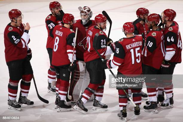 Goaltender Scott Wedgewood of the Arizona Coyotes is congratulated for his shutout by Tobias Rieder and Derek Stepan following the NHL game against...