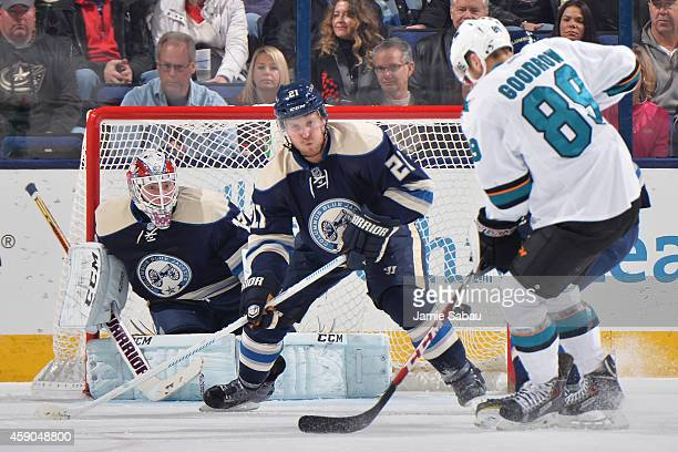 Goaltender Sergei Bobrovsky and James Wisniewski of the Columbus Blue Jackets follow the puck as Barclay Goodrow of the San Jose Sharks attempts to...