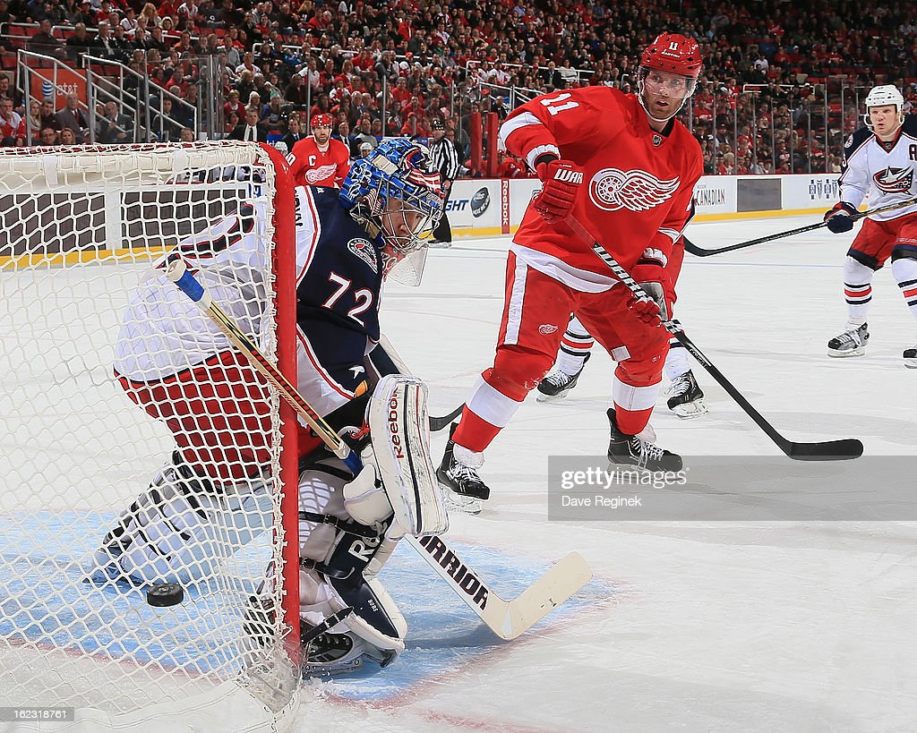 Goaltender Sergei Bobrovsky of the Columbus Blue Jackets and Dan Cleary of the Detroit Red Wings watch the puck go wide during a NHL game at Joe...
