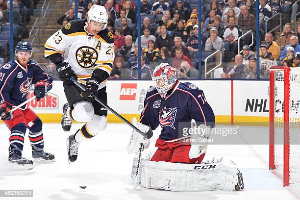 Goaltender Sergei Bobrovsky of the Columbus Blue Jackets defends the net as Chris Kelly of the Boston Bruins jumps to avoid the puck during the...