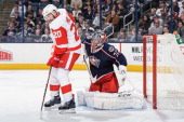 Goaltender Sergei Bobrovsky of the Columbus Blue Jackets defends the net as Drew Miller of the Detroit Red Wings skates in front on March 11 2014 at...
