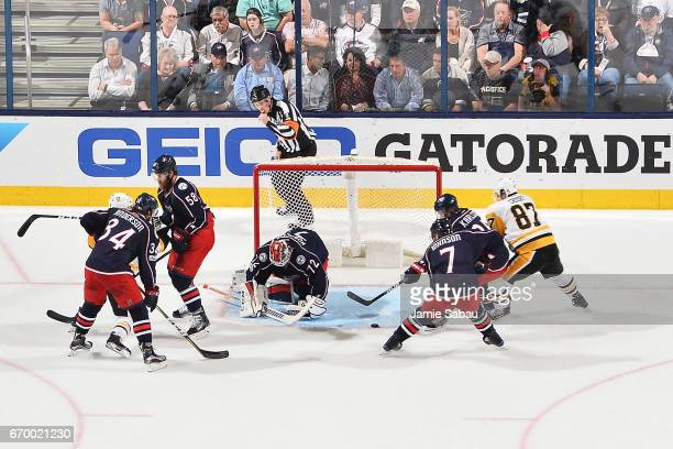 Goaltender Sergei Bobrovsky of the Columbus Blue Jackets defends the net as William Karlsson of the Columbus Blue Jackets and Sidney Crosby of the...