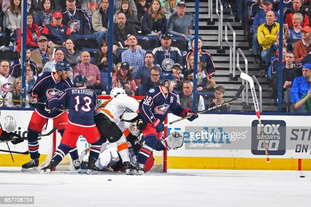 Goaltender Sergei Bobrovsky of the Columbus Blue Jackets falls to the ice as players from both teams battle for position in front of the net during...
