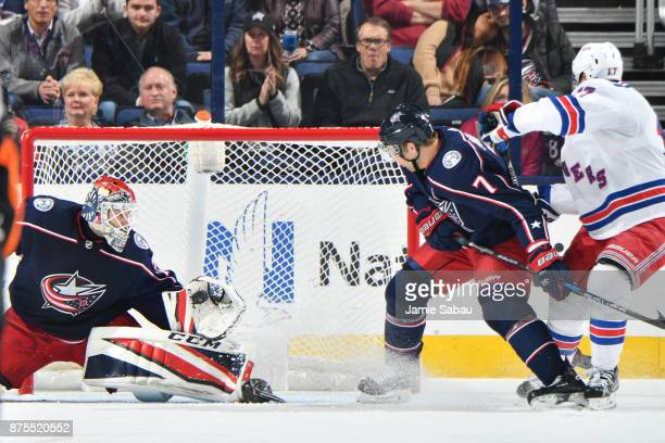 Goaltender Sergei Bobrovsky of the Columbus Blue Jackets makes a glove save as Jack Johnson of the Columbus Blue Jackets and Jesper Fast of the New...