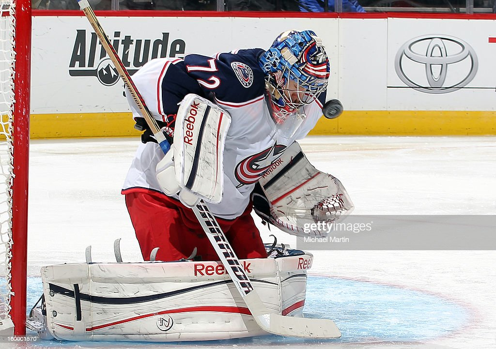 Goaltender <a gi-track='captionPersonalityLinkClicked' href=/galleries/search?phrase=Sergei+Bobrovsky&family=editorial&specificpeople=4488556 ng-click='$event.stopPropagation()'>Sergei Bobrovsky</a> #72 of the Columbus Blue Jackets makes a save off his facemask against the Colorado Avalanche at the Pepsi Center on January 24, 2013 in Denver, Colorado. Colorado beat Columbus 4-0.