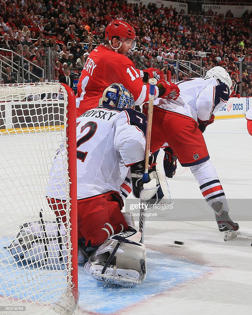 Goaltender Sergei Bobrovsky of the Columbus Blue Jackets makes a save as teammate Jack Johnson battles with Dan Cleary of the Detroit Red Wings...
