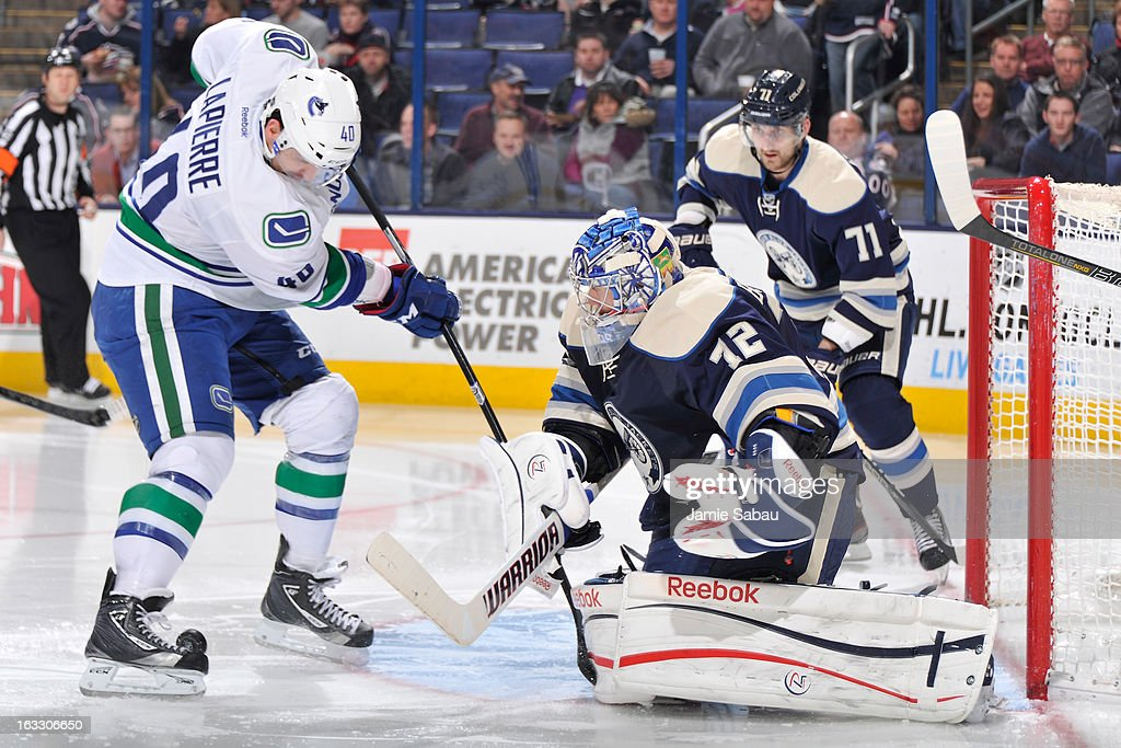 Goaltender <a gi-track='captionPersonalityLinkClicked' href=/galleries/search?phrase=Sergei+Bobrovsky&family=editorial&specificpeople=4488556 ng-click='$event.stopPropagation()'>Sergei Bobrovsky</a> #72 of the Columbus Blue Jackets stops a shot from <a gi-track='captionPersonalityLinkClicked' href=/galleries/search?phrase=Maxim+Lapierre&family=editorial&specificpeople=718385 ng-click='$event.stopPropagation()'>Maxim Lapierre</a> #40 of the Vancouver Canucks during the second period on March 7, 2013 at Nationwide Arena in Columbus, Ohio.