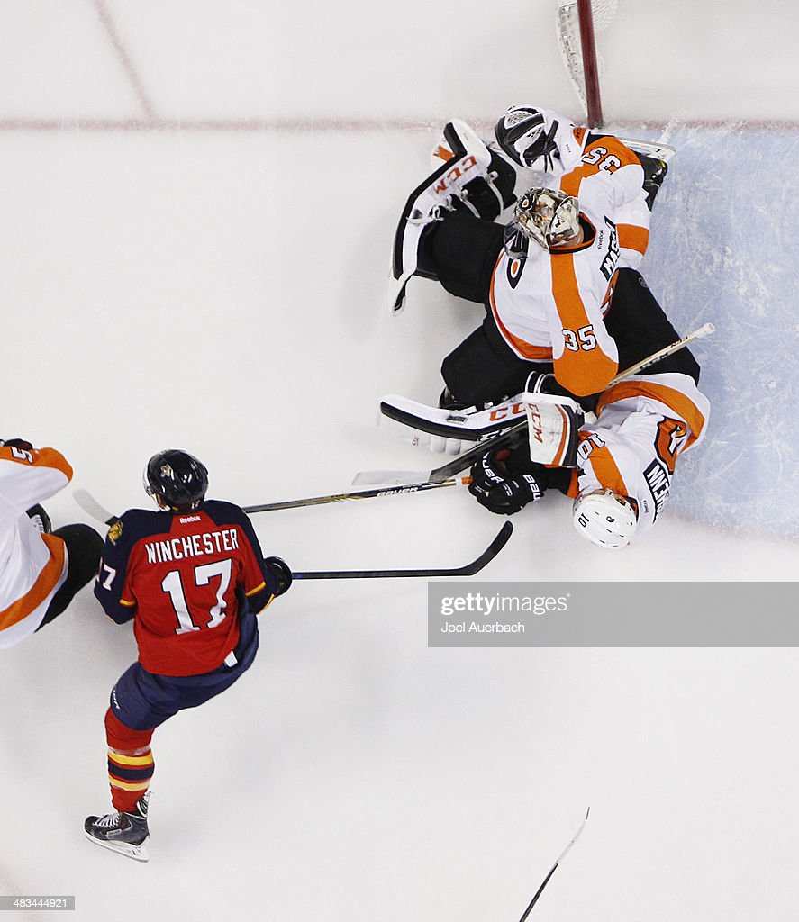 Goaltender Steve Mason #35 and Brayden Schenn #10 of the Philadelphia Flyers get tangled up in front of the net after a shot by Jesse Winchester #17 of the Florida Panthers at the BB&T Center on April 8, 2014 in Sunrise, Florida. The Flyers defeated the Panthers 5-2.
