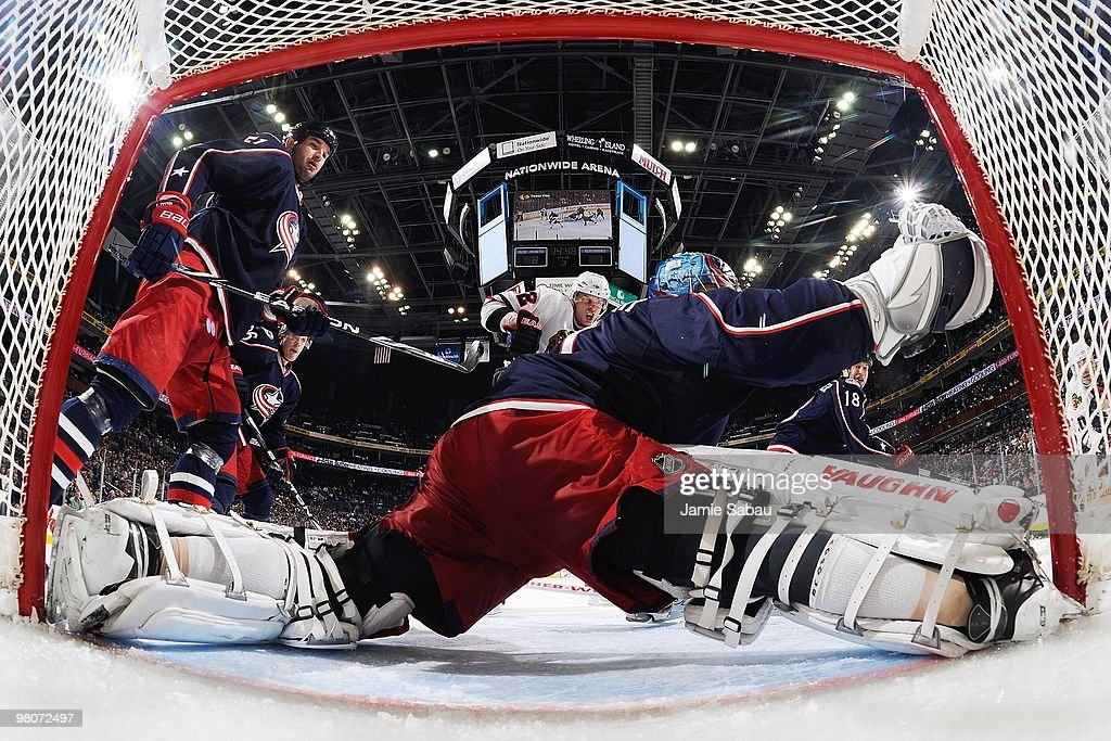 Goaltender Steve Mason of the Columbus Blue Jackets can't stop a shot by Tomas Kopecky of the Chicago Blackhawks as defenseman Fedor Tyutin of the...