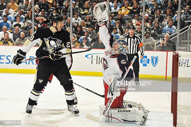 Goaltender Steve Mason of the Columbus Blue Jackets reaches up to snag the puck off a shot as Eric Tangradi of the Pittsburgh Penguins looks for the...