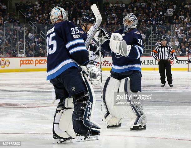 Goaltender Steve Mason of the Winnipeg Jets exchanges glove taps with teammate Connor Hellebuyck after being pulled during third period action...