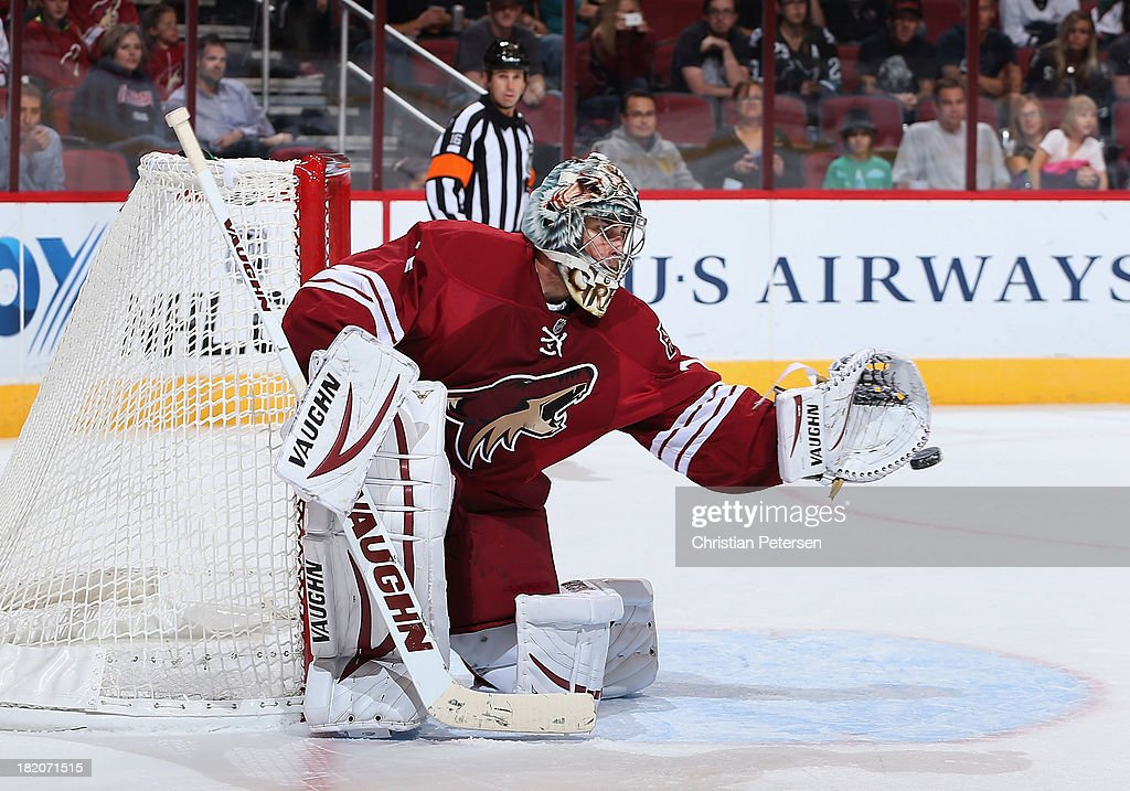 Goaltender <a gi-track='captionPersonalityLinkClicked' href=/galleries/search?phrase=Thomas+Greiss&family=editorial&specificpeople=695275 ng-click='$event.stopPropagation()'>Thomas Greiss</a> #1 of the Phoenix Coyotes attempts to make a glove save on the shot from the San Jose Sharks during the third period of the preseason NHL game at Jobing.com Arena on September 27, 2013 in Glendale, Arizona.