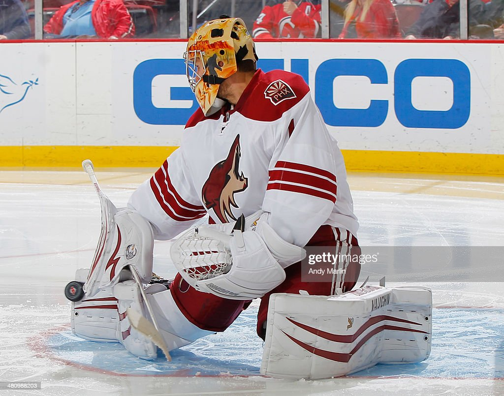 Goaltender <a gi-track='captionPersonalityLinkClicked' href=/galleries/search?phrase=Thomas+Greiss&family=editorial&specificpeople=695275 ng-click='$event.stopPropagation()'>Thomas Greiss</a> #1 of the Phoenix Coyotes makes a pad save against the New Jersey Devils during the game at the Prudential Center on March 27, 2014 in Newark, New Jersey.