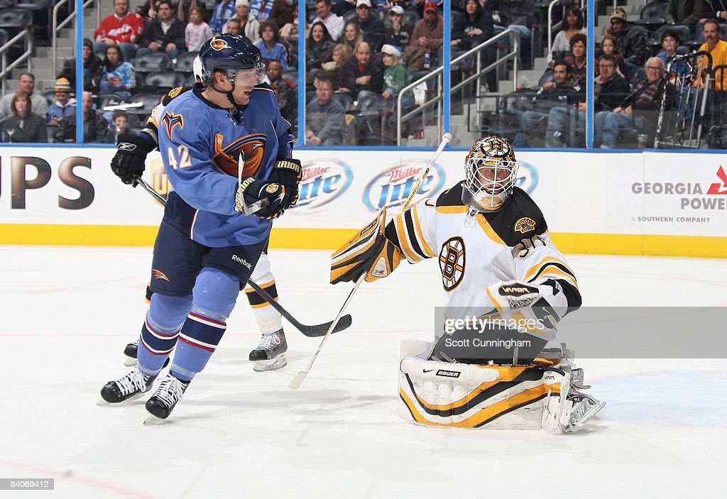 Goaltender Tim Thomas of the Boston Bruins makes a save against Joey Crabb of the Atlanta Thrashers at Philips Arena on December 12 2008 in Atlanta...
