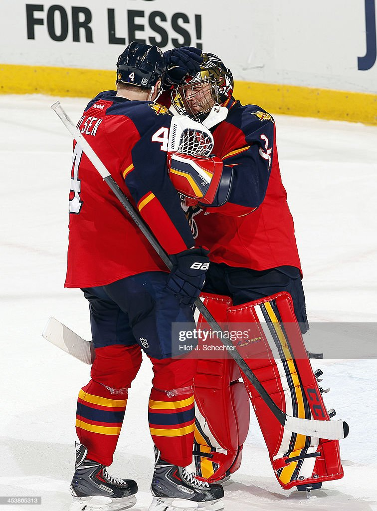 Goaltender Tim Thomas #34 of the Florida Panthers celebrates with teammate Dylan Olsen #4 their 5-2 win against the Winnipeg Jets at the BB&T Center on December 5, 2013 in Sunrise, Florida.