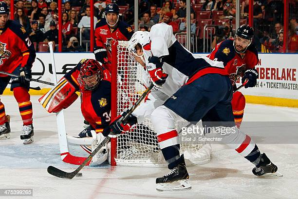 Goaltender Tim Thomas of the Florida Panthers defends the net against Jay Beagle of the Washington Capitals at the BBT Center on February 27 2014 in...