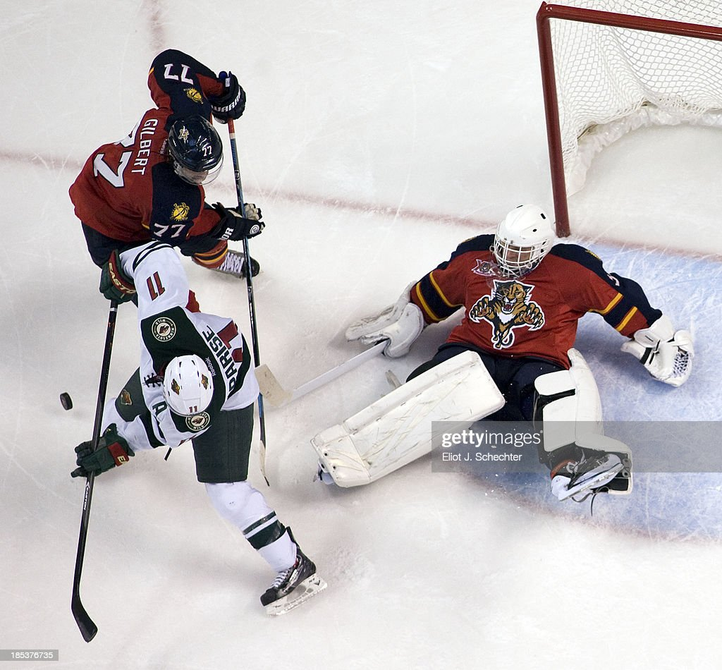 Goaltender Tim Thomas #34 of the Florida Panthers defends the net with the help of teammate <a gi-track='captionPersonalityLinkClicked' href=/galleries/search?phrase=Tom+Gilbert&family=editorial&specificpeople=687083 ng-click='$event.stopPropagation()'>Tom Gilbert</a> #77 against <a gi-track='captionPersonalityLinkClicked' href=/galleries/search?phrase=Zach+Parise&family=editorial&specificpeople=213606 ng-click='$event.stopPropagation()'>Zach Parise</a> #11 of the Minnesota Wild in overtime at the BB&T Center on October 19, 2013 in Sunrise, Florida.