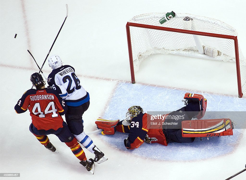 Goaltender Tim Thomas #34 of the Florida Panthers defends the net with the help of teammate <a gi-track='captionPersonalityLinkClicked' href=/galleries/search?phrase=Erik+Gudbranson&family=editorial&specificpeople=5741800 ng-click='$event.stopPropagation()'>Erik Gudbranson</a> #44 against <a gi-track='captionPersonalityLinkClicked' href=/galleries/search?phrase=Blake+Wheeler&family=editorial&specificpeople=716703 ng-click='$event.stopPropagation()'>Blake Wheeler</a> #26 of the Winnipeg Jets at the BB&T Center on December 5, 2013 in Sunrise, Florida.