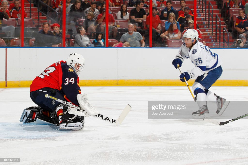 Goaltender Tim Thomas #34 of the Florida Panthers makes a kick save on a shot by <a gi-track='captionPersonalityLinkClicked' href=/galleries/search?phrase=Martin+St.+Louis&family=editorial&specificpeople=202067 ng-click='$event.stopPropagation()'>Martin St. Louis</a> #26 of the Tampa Bay Lightning at the BB&T Center on September 28, 2013 in Sunrise, Florida.