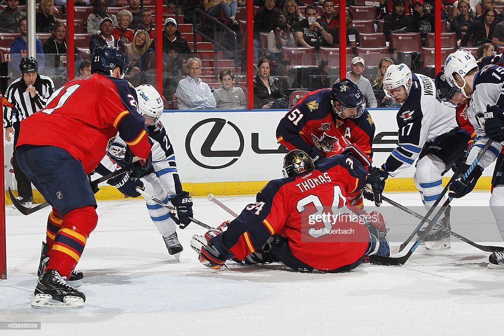 Goaltender Tim Thomas #34 of the Florida Panthers stops a shot by James Wright #17 with Eric Tangradi #27 of the Winnipeg Jets waiting for a rebound at the BB&T Center on December 5, 2013 in Sunrise, Florida.