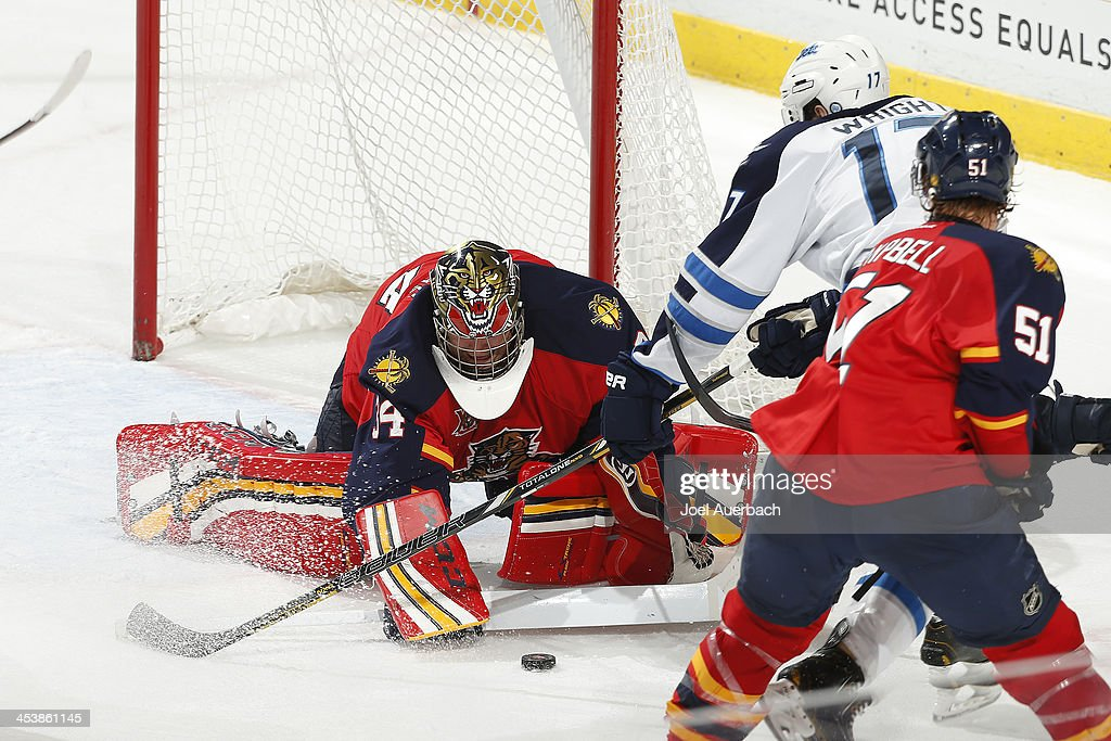 Goaltender Tim Thomas #34 of the Florida Panthers stops a shot by James Wright #17 of the Winnipeg Jets in the final minute of the third period at the BB&T Center on December 5, 2013 in Sunrise, Florida. The Panthers defeated the Jets 5-2.