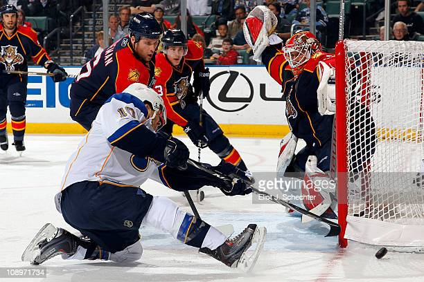 Goaltender Tomas Vokoun of the Florida Panthers defends the net with the help of teammate Dennis Wideman against Andy McDonald of the St Louis Blues...