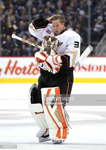 Goaltender Viktor Fasth of the Anaheim Ducks puts his mask back on after a break in play during second period action in an NHL game against the...