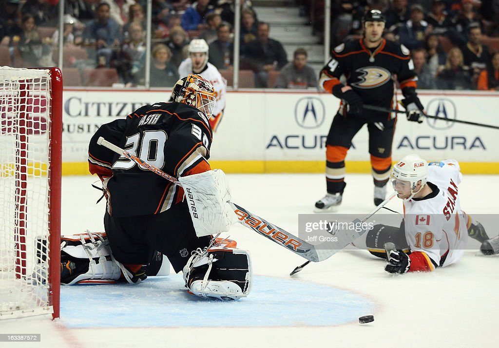 Goaltender Viktor Fasth #30 of the Ducks kicks out a shot, as Matt Stajan #18 of the Calgary Flames slides in front of the goal in the second period at Honda Center on March 8, 2013 in Anaheim, California. The Ducks defeated the Flames 4-0.