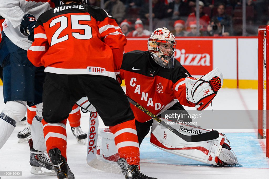 Goaltender <a gi-track='captionPersonalityLinkClicked' href=/galleries/search?phrase=Zachary+Fucale&family=editorial&specificpeople=9959699 ng-click='$event.stopPropagation()'>Zachary Fucale</a> #31 of Team Canada makes a glove save during the 2015 IIHF World Junior Hockey Championship game against Team Slovakia at the Bell Centre on December 26, 2014 in Montreal, Quebec, Canada.