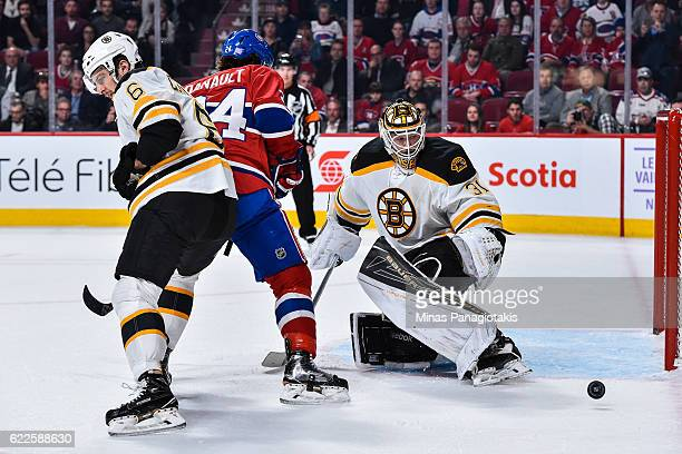 Goaltender Zane McIntyre watches the puck pass him while teammate Colin Miller of the Boston Bruins defends against Phillip Danault of the Montreal...