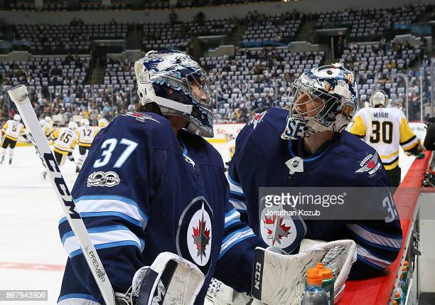 Goaltenders Connor Hellebuyck and Steve Mason of the Winnipeg Jets chat during the pregame warm up prior to NHL action against the Pittsburgh...