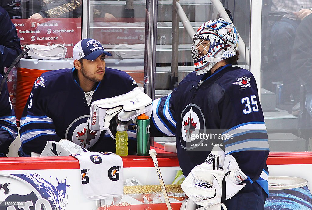Goaltenders Ondrej Pavelec #31 and <a gi-track='captionPersonalityLinkClicked' href=/galleries/search?phrase=Al+Montoya&family=editorial&specificpeople=213916 ng-click='$event.stopPropagation()'>Al Montoya</a> #35 of the Winnipeg Jets chat by the bench during a stoppage in play in third period action against the Detroit Red Wings at the MTS Centre on November 4, 2013 in Winnipeg, Manitoba, Canada.