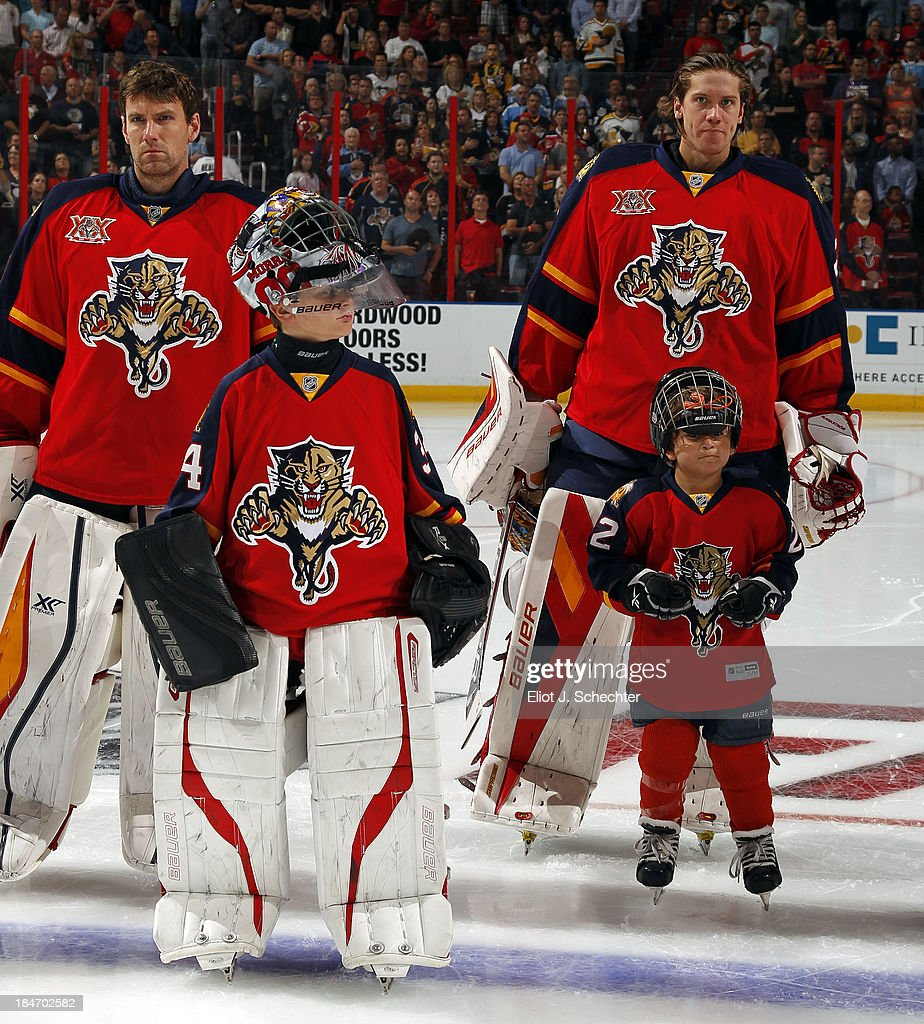 Goaltenders Scott Clemmensen and Jacob Markstrom of the Florida Panthers line up on the ice with a junior guest skaters prior to the start of the...