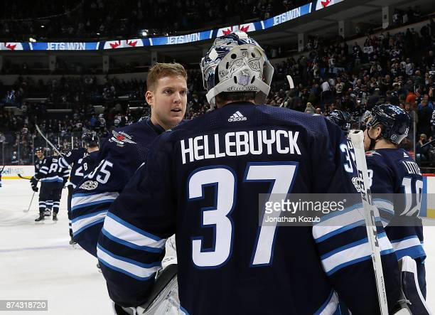 Goaltenders Steve Mason and Connor Hellebuyck of the Winnipeg Jets celebrate following a 41 victory over the Arizona Coyotes at the Bell MTS Place on...
