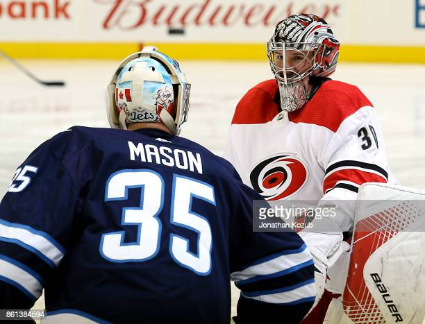 Goaltenders Steve Mason of the Winnipeg Jets and Cam Ward of the Carolina Hurricanes chat during the pregame warm up prior to NHL action at the Bell...