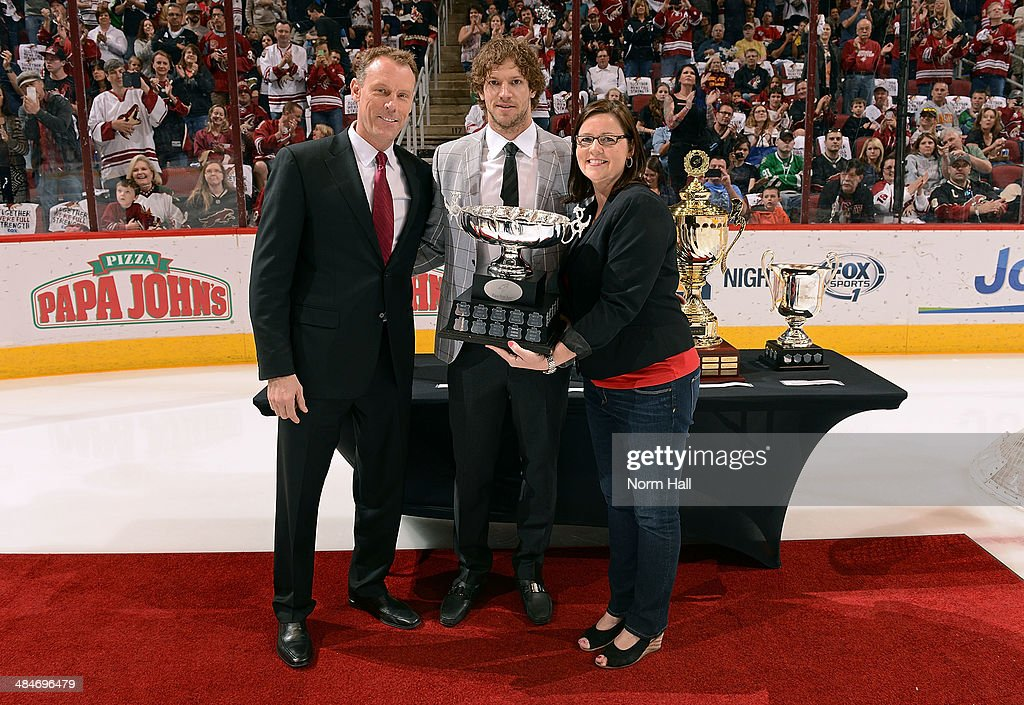 Goaltending coach <a gi-track='captionPersonalityLinkClicked' href=/galleries/search?phrase=Sean+Burke&family=editorial&specificpeople=204179 ng-click='$event.stopPropagation()'>Sean Burke</a> (L) and Nancy Wasser of Ganem Jewelers present Mike Smith #41 of the Phoenix Coyotes the Three Star Award trophy before the start of the final game of the season against the Dallas Stars at Jobing.com Arena on April 13, 2014 in Glendale, Arizona.