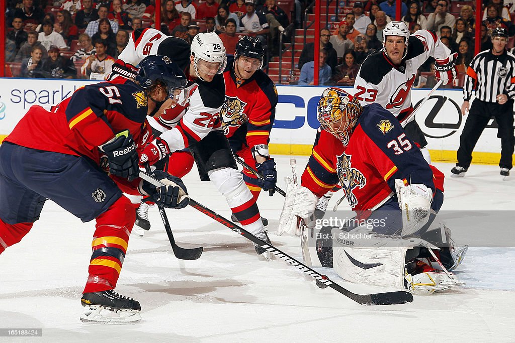 Goaltenter Jacob Markstrom #35 of the Florida Panthers defends the net with the help of teammate Brian Campbell #51 against Patrik Elias #26 of the New Jersey Devils at the BB&T Center on March 30, 2013 in Sunrise, Florida.