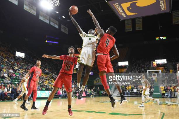 Goanar Mar of the George Mason Patriots drives to the basket over Zeno Lake and Tavrion Dawson of the Cal State Northridge Matadors during a college...