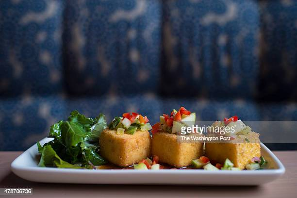 Goat cheese grits poppers with a smoked jalapeno sauce and apple salsa at the Tupelo Honey Cafe in Arlington VA on Wednesday June 10 2015