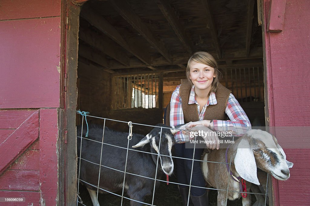 A goat farm. A young girl leaning on the barrier of the goat shed, with two animals peering out. : Stock Photo