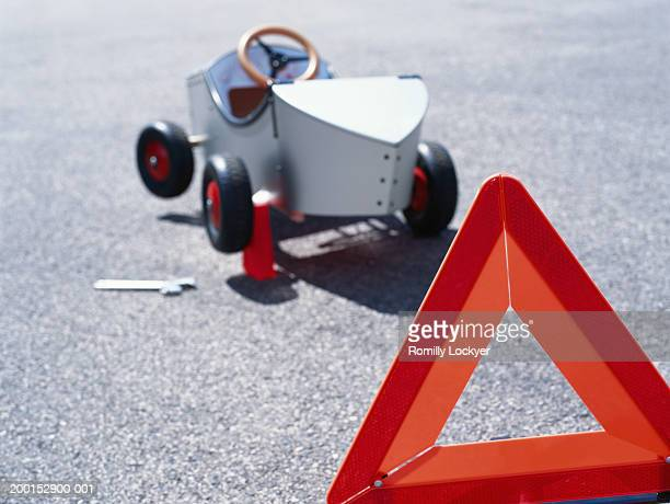 Go-cart and hazard warning triangle on road (focus on triangle)