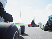 Go-cart drivers racing on track, rear view (blurred motion)