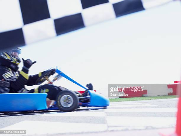 Go-cart racer approaching finish line, side view (blurred motion)