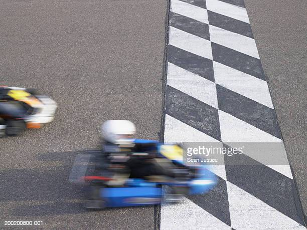 Go-cart racer crossing finish line, elevated view (blurred motion)