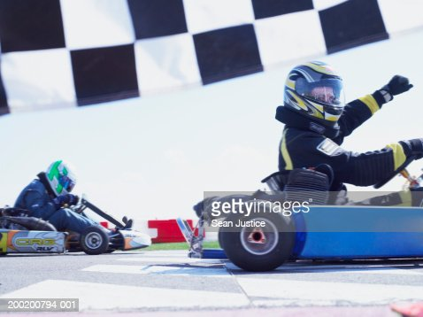 Go-cart racer crossing finish line, raising arm, side view : Stock Photo